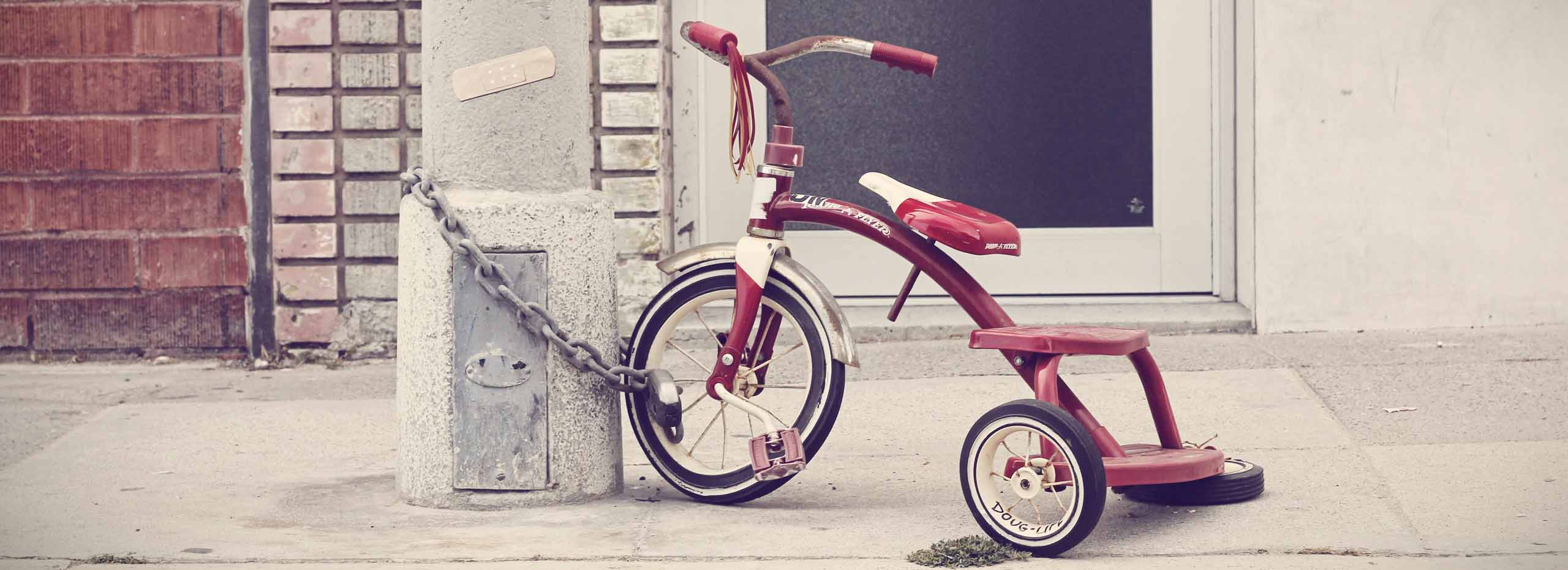A child's tricycle is locked to a streetlamp in a city environment
